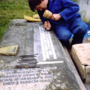 stonemason hand cutting a raised lead inscription