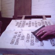 stonemason finishing a lead filled inscription